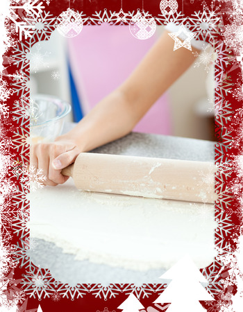 gratified: Smiling woman preparing a cake the kitchen  against christmas themed frame