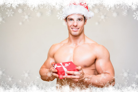 Shirtless macho man in santa hat holding gift against fir tree forest and snowflakes