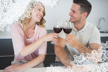 Couple toasting red wine glasses at table against snowflake frame photo