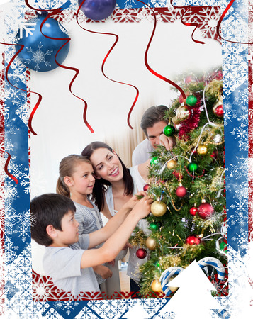 Happy family decorating a Christmas tree with boubles against christmas themed frame photo