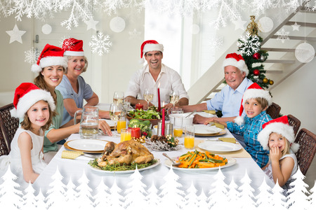 Happy family in Santa hats having Christmas meal against fir tree forest and snowflakes photo