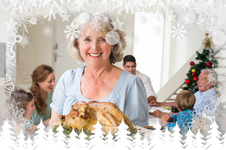 Happy grandmother with Christmas meal against fir tree forest and snowflakes photo