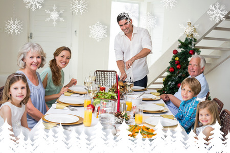 Family having Christmas meal at dining table against fir tree forest and snowflakes photo