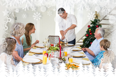 Father serving Christmas meal to family against fir tree forest and snowflakes photo