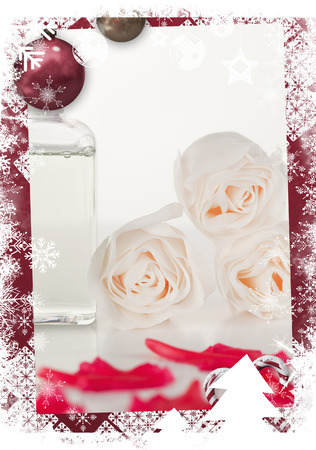 Christmas themed frame against pink petals with a glass flask and roses photo