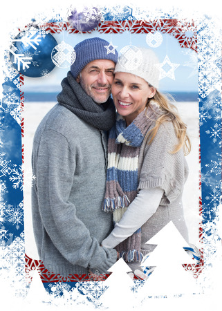 Smiling couple standing on the beach in warm clothing against christmas themed frame photo
