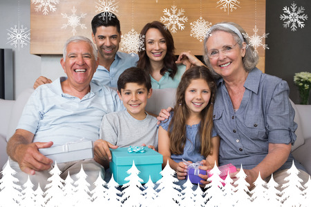 Extended family on sofa with gift boxes in living room against fir tree forest and snowflakes photo