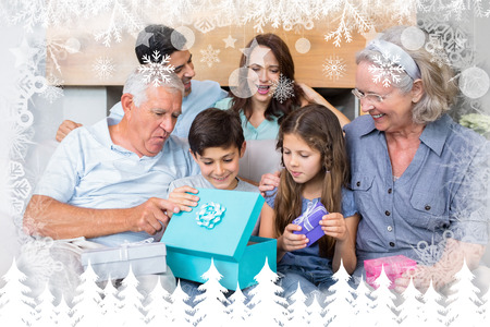 Extended family sitting on sofa with gift boxes in living room against fir tree forest and snowflakes photo