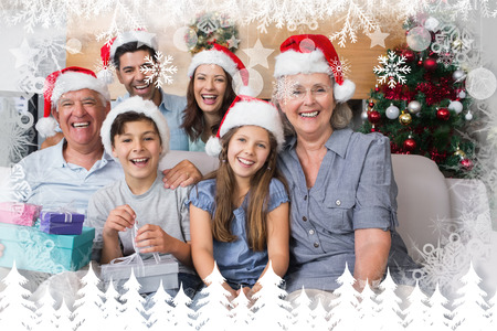 Extended family in Christmas hats with gift boxes in living room against fir tree forest and snowflakes photo