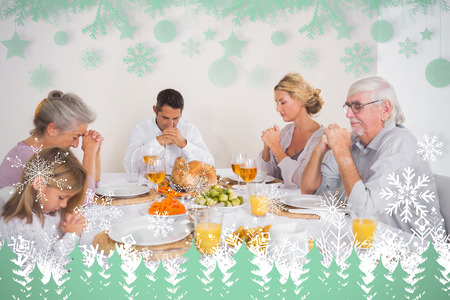Family saying grace before eating a turkey against snowflakes and fir trees in green photo