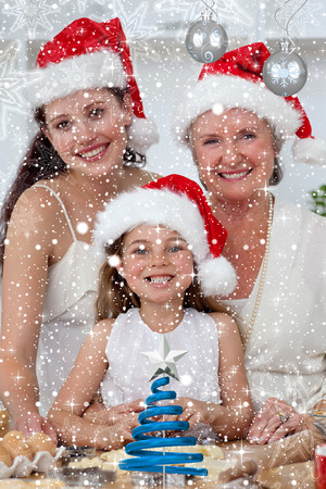 Daughter mother and grandmother baking Christmas sweets against twinkling stars photo