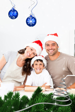 Happy family baking christmas cookies together against twinkling stars photo
