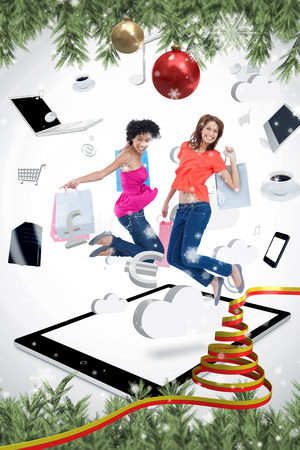 Two smiling women jumping on a tablet pc  against snow falling photo