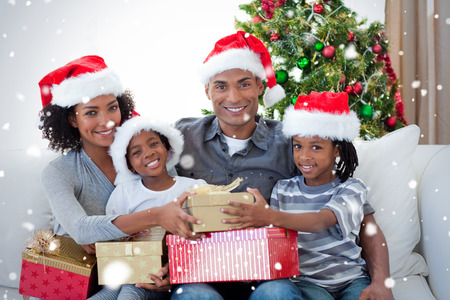Smiling family sharing Christmas presents against snow falling photo