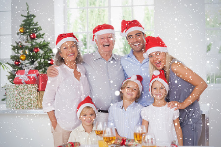 Composite image of Family posing for photo against snow falling photo