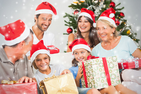 Composite image of Happy family at christmas swapping gifts against snow
