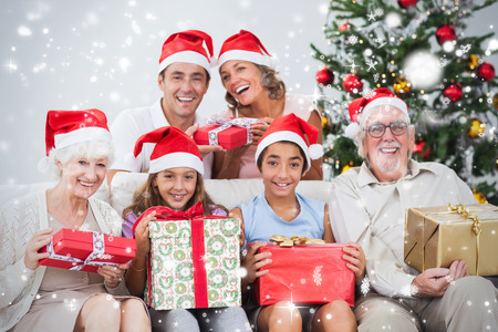 Composite image of Family exchanging christmas presents against snow falling photo