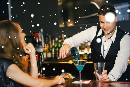 Handsome bartender serving cocktail to attractive woman against snow photo