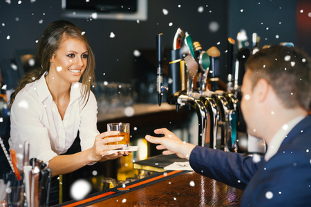 Beautiful waitress serving handsome businessman against snow falling photo