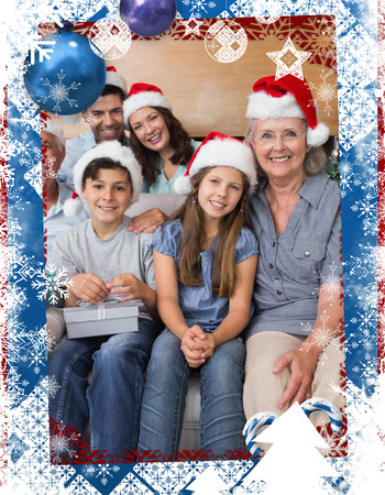 Extended family in Christmas hats with gift boxes in living room against christmas themed frame Stock Photo