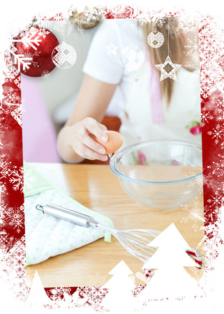 gratified: Portrait of a cute woman preparing a meal in the kitchen against christmas themed frame Stock Photo