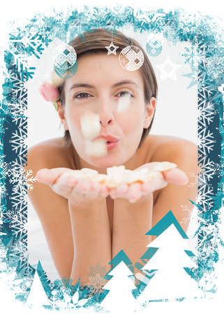 Beautiful happy woman blowing flower petals at spa center against christmas themed frame photo