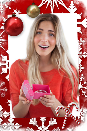 Surprised blonde woman opening gift against christmas themed page photo