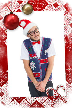 Geeky hipster in santa hat against christmas themed page photo