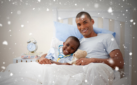 Composite image of father with his sick child against snow falling photo