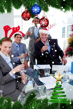 Manager and his team toasting with Champagne at a Christmas party against snow falling photo
