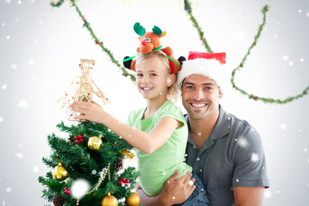 Happy father and daughter decorating together the christmas tree against snow falling photo