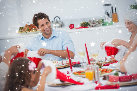 family dining: Composite image of Cheerful family dining together against snow