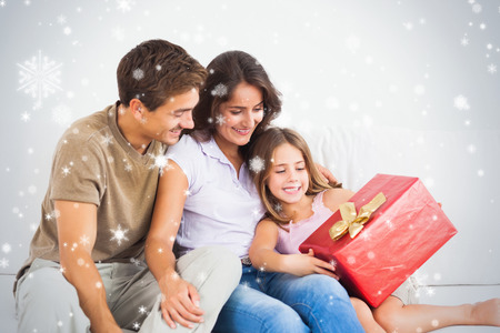 Composite image of Parents offering a gift against snow falling photo