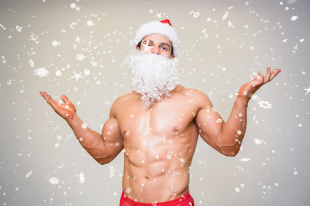 Portrait of shirtless macho man with fake santa beard against snow falling photo