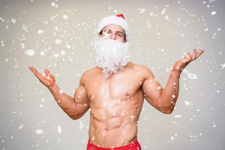 Portrait of shirtless macho man with fake santa beard against snow falling photo