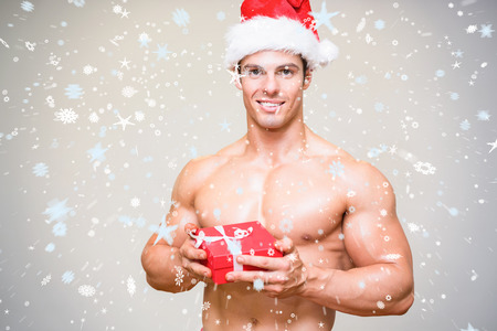 Composite image of Shirtless macho man in santa hat holding gift against snow photo
