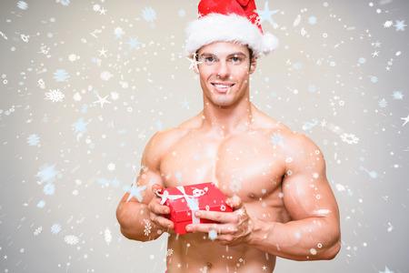 sin camisa: Imagen compuesta del hombre macho descamisado en sombrero de santa celebración de regalo contra la nieve