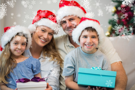 Family wearing Christmas hat while holding presents against snowflakes photo