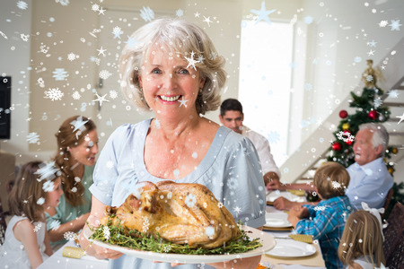 Composite image of Happy grandmother with Christmas meal against snow photo