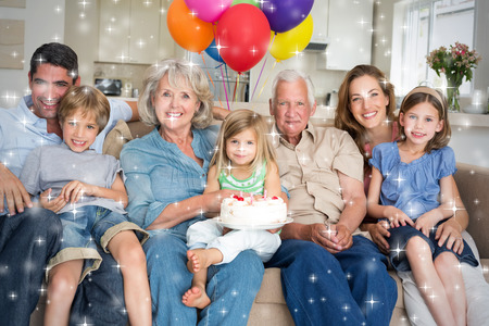 Composite image of Multigeneration family celebrating girls birthday against snow photo