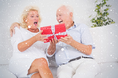 Composite image of Surprising old woman receiving a gift against snow falling photo