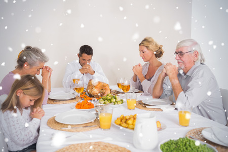 Composite image of Family saying grace before eating a turkey against snow falling photo
