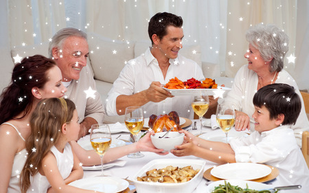 family holiday: Composite image of Family having a big dinner at home against snow Stock Photo