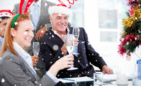 business: Composite image of Businessman team celebrating christmas  against snow falling