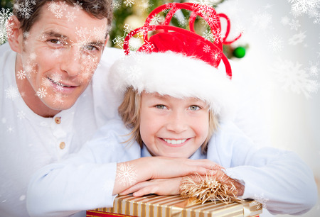 Composite image of Bright father celebrating christmas with his son against snowflakes photo