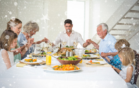 praying together: Composite image of Family praying together before meal at dining table against snow
