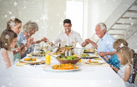 family praying: Imagen compuesta de Familia orar juntos antes de la comida en la mesa de comedor contra la nieve Foto de archivo