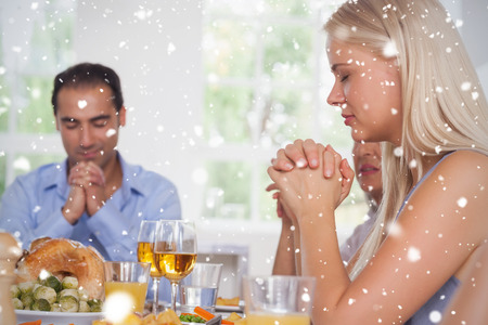 Composite image of Woman saying grace with family before dinner against snow falling photo