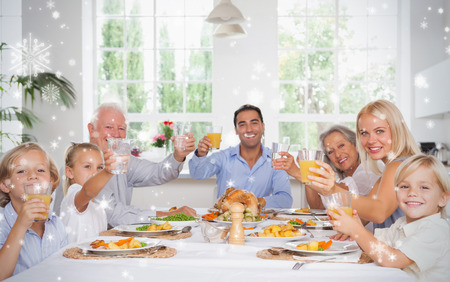 Composite image of Happy family toasting at thanksgiving dinner against snow falling Stock Photo