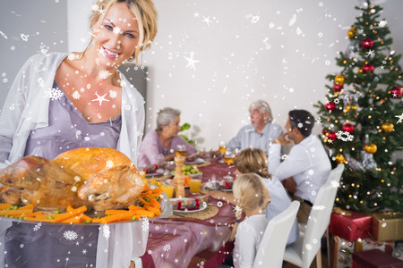 Composite image of Proud mother showing roast turkey against snow falling photo